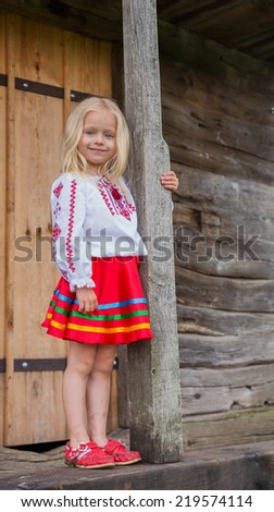 Little beautiful ukrainian girl standing near old national wooden house in national dress and watching you - stock photo
