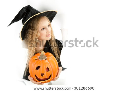 little beautiful witch with Jack O' Lantern peeking through a hole in white paper
