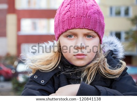 Little beauty blond girl looks thoughtfully into the distance. Outdoor street city portrait. - stock photo