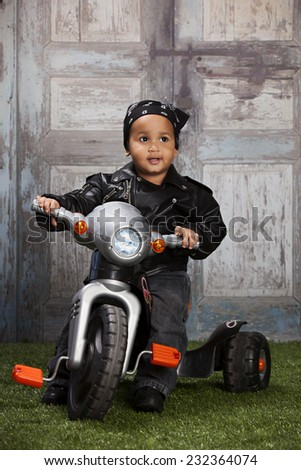 Little Biker.  Adorable toddler riding a toy bike.   - stock photo