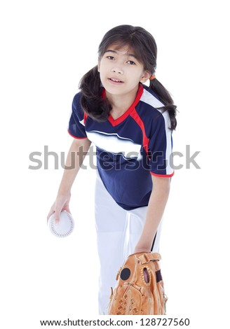 Little biracial asian girl in softball team uniform ready to throw a pitch - stock photo