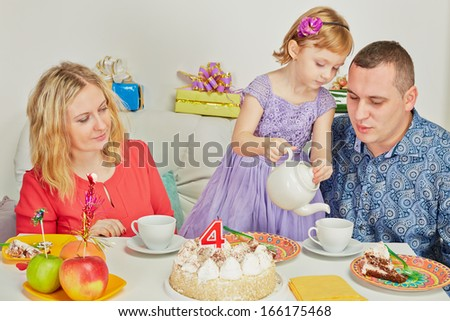 Little birthday girl pours out tea to her parents sitting at birthday table