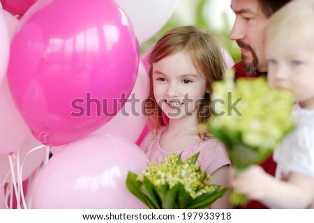 Little birthday girl with pink balloons and flowers - stock photo