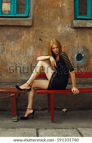 Little black dress and high heels concept. Portrait of a beautiful fashionable woman in black cocktail dress and high heel shoes sitting in old italian yard. Bright colors. Vogue style. Outdoor shot - stock photo