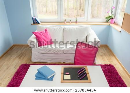 Little blackboard and books on white desk in study room - stock photo