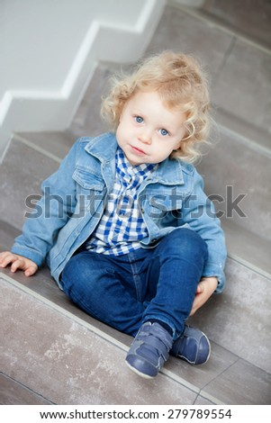 Little blond baby sitting on the stairs at home - stock photo