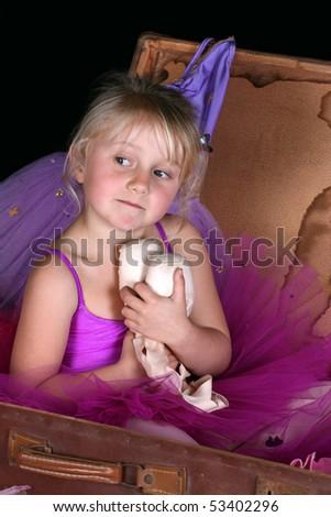 Little blond ballerina wearing a purple tutu - stock photo