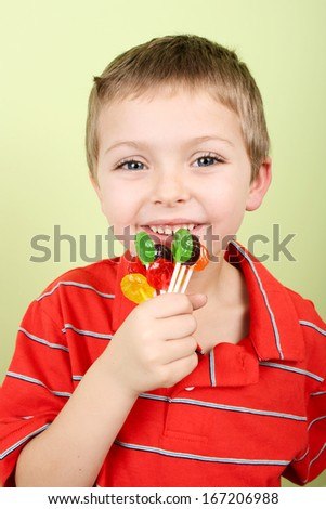 Little blond boy against yellow background eating candy - stock photo