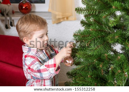 Little blond boy decorating Christmas tree at home - stock photo