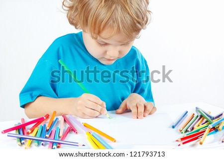 Little blond boy draws with color pencils on a white background