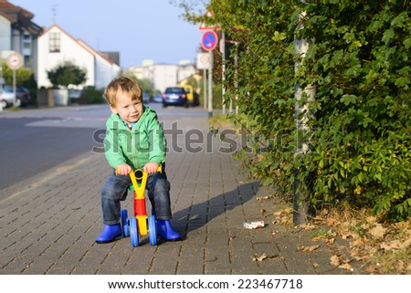 Little blond boy driving his bycicle, outdoor, autumn