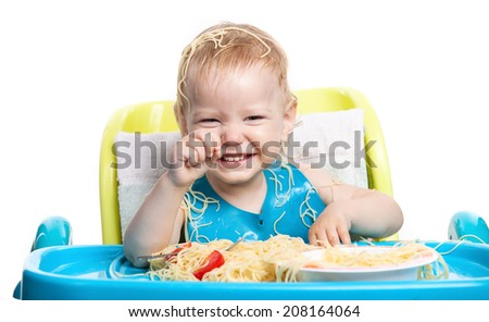 Little blond boy eating spaghetti and laughing - stock photo