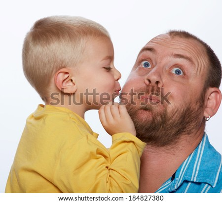 Little blond boy gives his father a kiss on isolated studio background