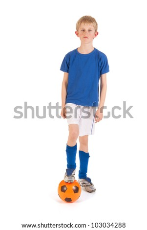 Little blond boy is playing soccer in the studio - stock photo