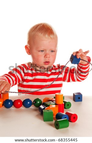 Little blond boy is playing with colorful wooden beads