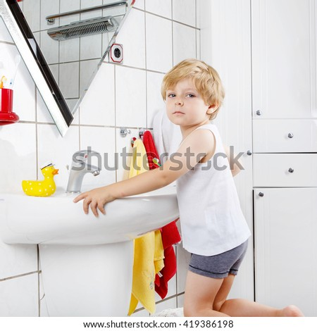 Little blond boy learning brushing his teeth in domestic bath. Kid learning how to stay healthy. Health care concept. - stock photo