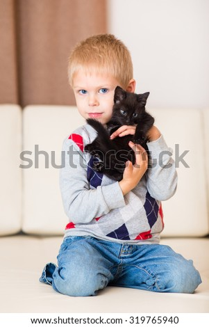 little blond boy playing with a black kitten on a white leather couch