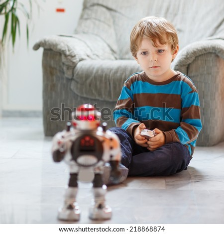 Little blond boy playing with robot toy at home, indoor - stock photo