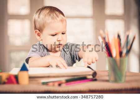 Little blond boy standing drawing with crayons - stock photo