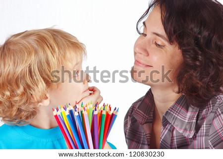 Little blond boy with his mother with color pencils on a white background - stock photo