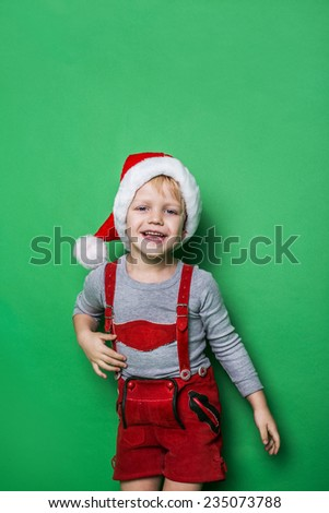 Little blond boy with Santa Claus cap smiling. Studio portrait over green background - stock photo