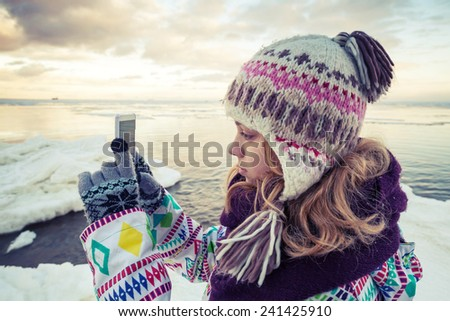 Little blond Caucasian girl taking pictures on her smartphone photo camera, vintage toned photo, insagram style photo - stock photo
