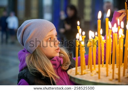 Little blond Caucasian girl with candles in Orthodox Russian Church - stock photo