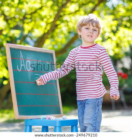 Little blond child at blackboard practicing writing letters and mathematics, outdoor school or nursery. Kid learning and schoolboy concept. On summer sunny day. Back to school. - stock photo