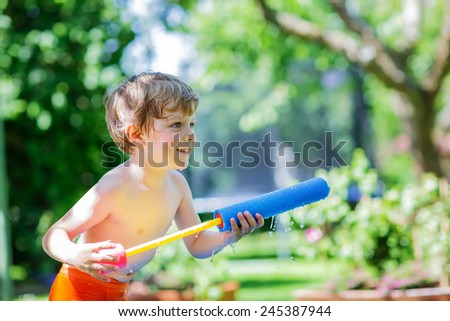 Little blond child having fun with splashing water in summer garden, playing water gun. Outdoors leisure with kids in summer, on sunny hot day. - stock photo
