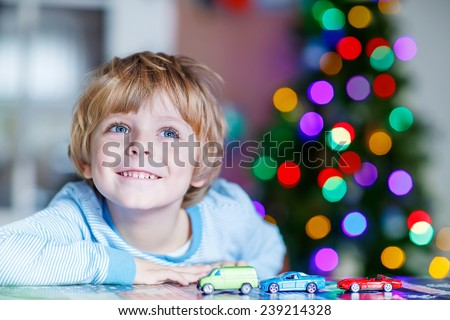 Little blond child playing with cars and toys at home, indoor. Cute happy funny boy having fun with gifts. Colorful lights on background - stock photo