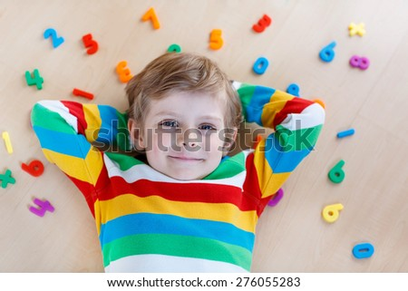 Little blond child playing with lots of colorful plastic digits or numbers, indoor. Kid boy wearing colorful shirt and having fun with learning math