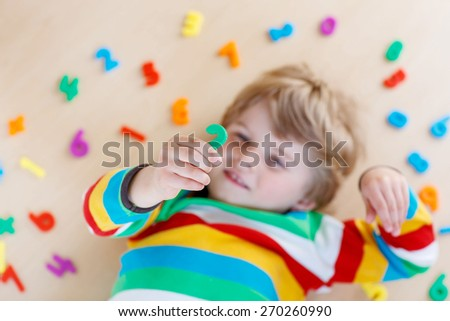 Little blond child playing with lots of colorful plastic digits or numbers, indoor. Selective focus on kid's hand - stock photo