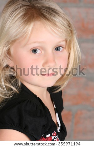 Little blond girl against a brick background - stock photo