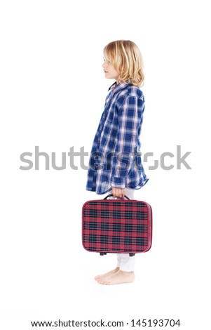 Little blond girl carrying a small tartan suitcase in a matching plaid shirt and bare feet posing standing sideways isolated on white - stock photo