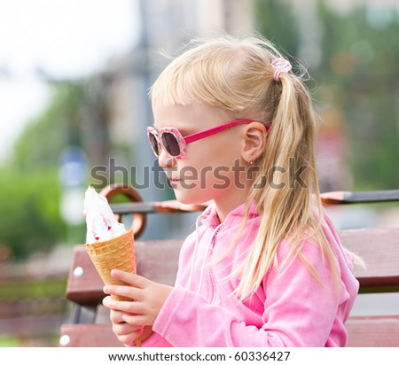Little blond girl eating ice-cream - stock photo