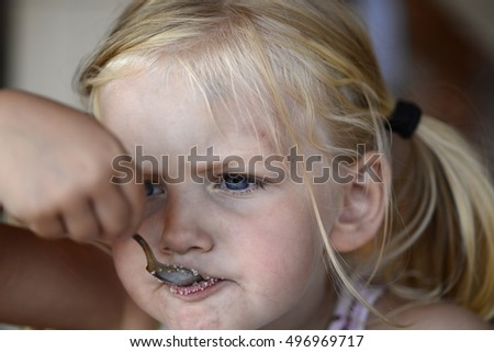 Little blond girl eating sugar with spoon.