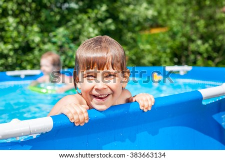 Little blond girl enjoying summertime  in a pool