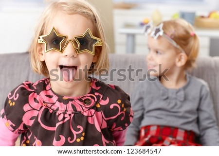 Little blond girl having fun at home, sticking tongue, wearing funny star shaped glasses, little sister in the background.