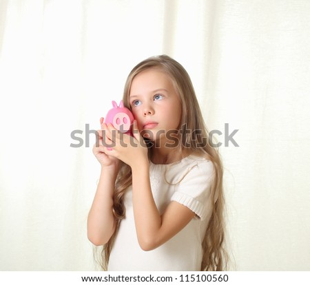 Little blond girl hearing how much money in piggy moneybox and dreaming about future purchase - stock photo
