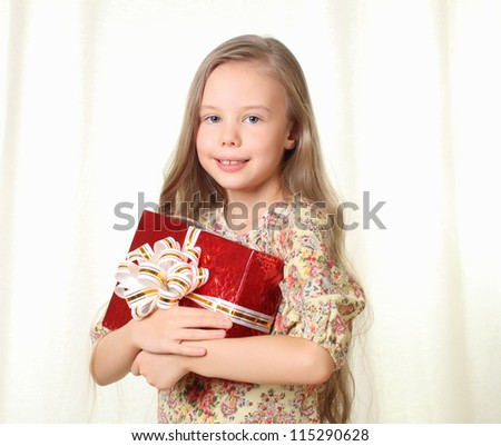 Little blond girl holding a red glamorous gift - stock photo