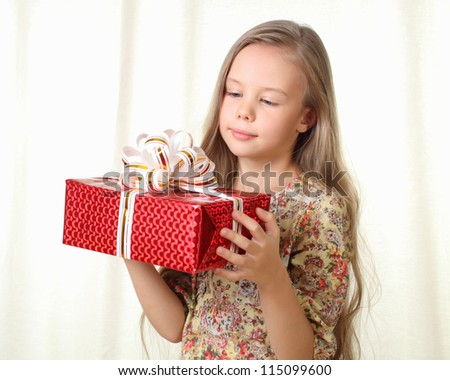 Little blond girl holding a red glamorous gift and looking on it - stock photo