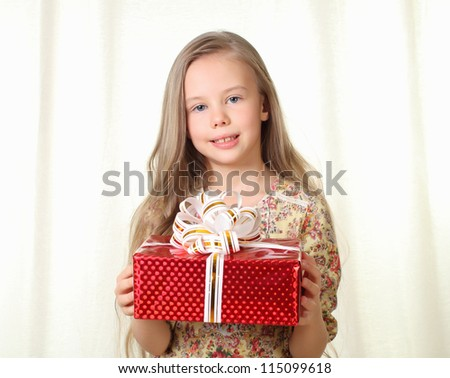 Little blond girl holding a red glamorous gift and looking to camera - stock photo