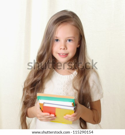 Little blond girl holding diffenet books and smiling - stock photo
