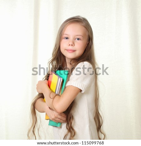 Little blond girl holding different books and smiling - stock photo