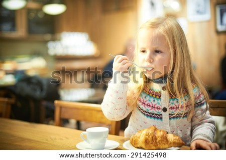 Little blond girl in a cafe drinking hot milk - stock photo