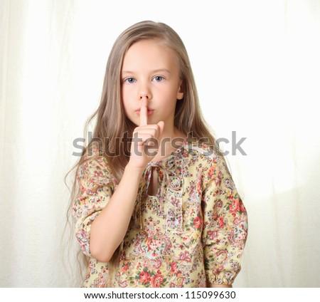 Little blond girl keeping silence holding forefinger near lips - stock photo