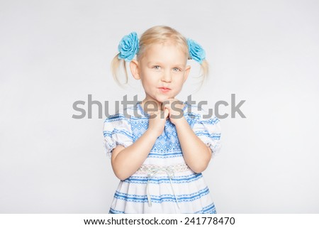 Little blond girl on a white background standing with folded hands - stock photo