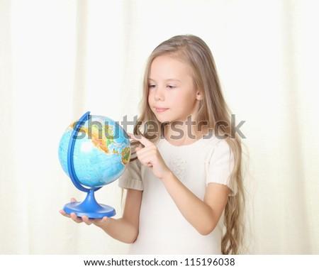 Little blond girl picking a globe by finger - stock photo