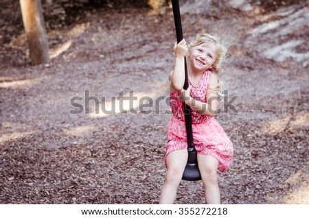 little blond girl playing in the playground - stock photo