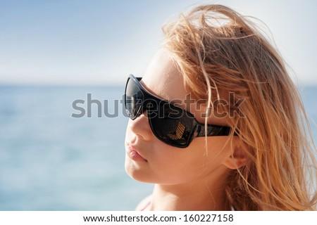 Little blond girl portrait with sunglasses on the summer sea coast - stock photo